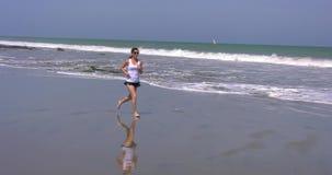 Femme courant sur le rivage avec les cieux bleus banque de vidéos