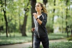 Femme courante en stationnement en formation d'été Jeune modèle de forme physique de sport dans des vêtements courants sportifs photos libres de droits