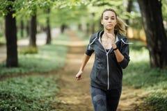 Femme courante en stationnement en formation d'été Jeune modèle de forme physique de sport dans des vêtements courants sportifs images libres de droits