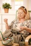 Femme cousant dans le fauteuil Images libres de droits