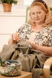 Femme cousant dans le fauteuil Photographie stock libre de droits