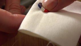 Femme cousant le bouton français de drapeau Fait dans les Frances et les concepts faits main tir du plan rapproché 4K clips vidéos