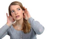 Femme écoutant prudemment Photographie stock libre de droits