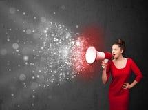 Femme criant dans le mégaphone et l'explo rougeoyant de particules d'énergie Photos stock