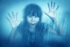 Femme criant derrière le verre de fenêtre souillé ou sale Image libre de droits