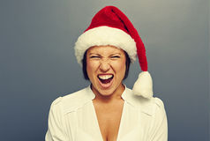 Femme criarde dans le chapeau rouge de Noël au-dessus du gris photographie stock