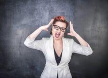 Femme criarde fâchée sur le fond de tableau noir photographie stock libre de droits