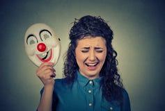 Femme criarde pleurante bouleversée tenant un masque de clown exprimant la gaieté photographie stock