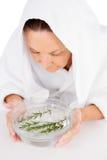 Femme cuisant le visage à la vapeur avec le romarin dans la cuvette de l'eau Image stock