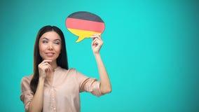 Femme curieuse tenant le signe allemand de drapeau, apprenant la langue, éducation à l'étranger banque de vidéos