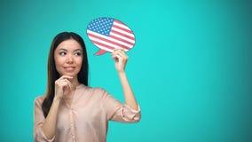 Femme curieuse tenant le signe de drapeau des Etats-Unis, apprenant la langue, éducation à l'étranger clips vidéos
