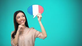 Femme curieuse tenant le signe français de drapeau, apprenant la langue, éducation à l'étranger banque de vidéos