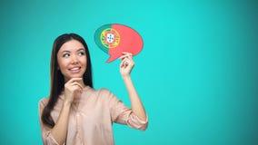 Femme curieuse tenant le signe portugais de drapeau, apprenant la langue, éducation à l'étranger clips vidéos