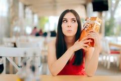 Femme curieuse vérifiant le boîte-cadeau une date photographie stock