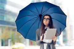 Femme déçue avec les verres, la Tablette et le parapluie dans la ville photo stock