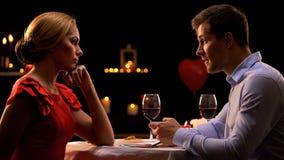 Femme déçue regardant l'ami à l'aide du smartphone pendant la date romantique photo stock