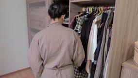 Femme décidant quoi porter près de la garde-robe banque de vidéos