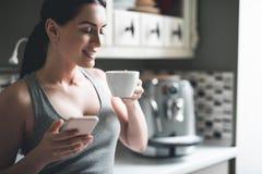 Femme décontractée buvant la boisson chaude et à l'aide du téléphone à la maison image libre de droits