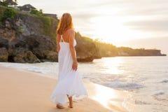 Femme décontractée dans la robe blanche marchant sur la plage dans la soirée photos libres de droits