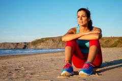 Femme décontractée de forme physique se reposant à la plage Photo stock