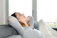 Femme décontractée heureuse se reposant sur un divan à la maison Photos libres de droits