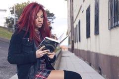 Femme décontractée lisant un livre se reposant dans l'arrière-cour Photos stock