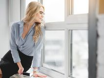 Femme décontractée s'asseyant sur le rebord de fenêtre avec le dispositif Images libres de droits