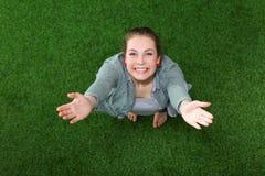 Femme décontractée se trouvant sur l'herbe avec des mains sur la tête Images libres de droits