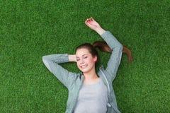 Femme décontractée se trouvant sur l'herbe avec des mains sur la tête Photographie stock