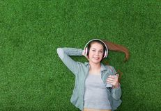 Femme décontractée se trouvant sur l'herbe avec des mains sur la tête Photo libre de droits