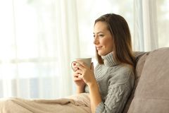 Femme décontractée songeuse tenant le café à la maison photographie stock libre de droits