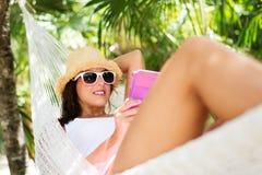 Femme décontractée sur la lecture d'hamac image stock
