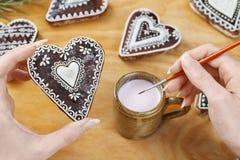 Femme décorant des biscuits de pain d'épice dans la forme de coeur Photo stock