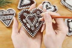 Femme décorant des biscuits de pain d'épice dans la forme de coeur Images stock
