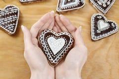Femme décorant des biscuits de pain d'épice dans la forme de coeur Images libres de droits
