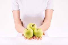 Femme démontrant trois pommes vertes Photos libres de droits