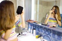Femme désespérée au sujet de la perte des cheveux devant le miroir dans la salle de bains images stock