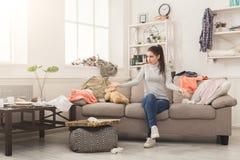 Femme désespérée s'asseyant sur le sofa dans la chambre malpropre photographie stock libre de droits