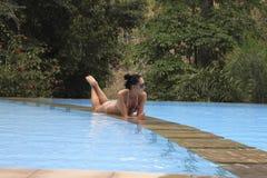 Femme détendant à l'intérieur de la piscine dans une station de vacances tropicale de luxe Image stock