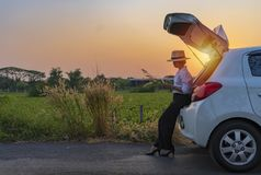 Femme détendant à l'intérieur du tronc de voiture et observant sur la belle nature photo stock