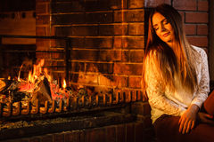 Femme détendant à la cheminée Maison d'hiver Image libre de droits
