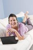 Femme détendant à la maison sur le sofa avec l'ordinateur portatif photos libres de droits