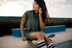 Femme détendant à la musique de écoute de parc de patin Photos stock