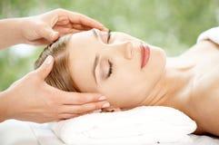 Femme détendant à la station thermale ayant un massage facial Photos libres de droits