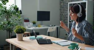 Femme détendant au travail écoutant la musique dans des écouteurs dansant utilisant l'ordinateur portable clips vidéos