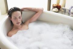 Femme détendant avec des yeux fermés dans la baignoire Photos libres de droits