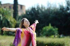 Femme détendant avec les bras et le visage ouverts au soleil Photo stock