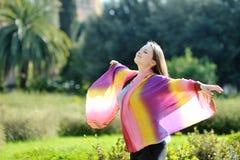 Femme détendant avec les bras et le visage ouverts au soleil Image stock