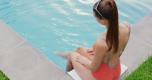 Femme détendant avec ses pieds dans la piscine à l'arrière-cour 4k banque de vidéos