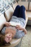 Femme détendant avec un livre sur le divan Image libre de droits